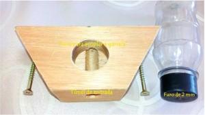 Figura 1. Detalhes alimentador modelo Roso, composto por uma base de madeira, uma garrafa de plástico transparente e dois parafusos para fixação na colmeia. A base de madeira possui dois furos, um para acesso das abelhas à colmeia (túnel de entrada) e outro para acoplar a garrafa que contém o alimento liquido. A tampa da garrafa possui um furo de 2 mm de diâmetro.